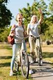 Adolescente alegre que monta una bicicleta con su abuela Fotos de archivo libres de regalías
