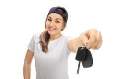 Adolescente alegre que muestra un par de llaves del coche Imagen de archivo