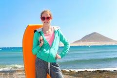 Adolescente alegre que se coloca con la tabla hawaiana en Océano Atlántico Fotos de archivo