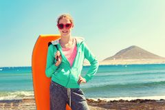 Adolescente alegre que se coloca con la tabla hawaiana en Océano Atlántico Fotos de archivo libres de regalías