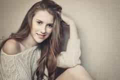 Adolescente alegre que se sienta contra fondo y la sonrisa neutrales Foto de archivo
