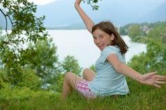 Adolescente alegre que se sienta en la hierba Fotos de archivo libres de regalías