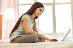 Adolescente alegre que usa el ordenador portátil y la sonrisa Foto de archivo