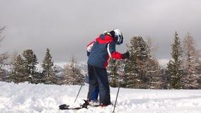 Adolescente alla stazione sciistica Il ragazzo attacca gli sci agli scarponi da sci Un bambino in una giacca a vento e casco cont archivi video
