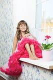 Adolescente allegro della ragazza che si siede sul windowsil nella sala Immagine Stock