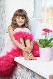 Adolescente allegro della ragazza che si siede sul windowsil nella sala Fotografie Stock