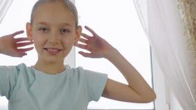 Adolescente allegro della ragazza divertendosi e ballando macchina fotografica anteriore sul fondo della finestra archivi video