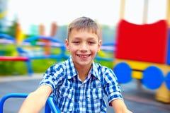 Adolescente allegro divertendosi sulla rotonda, campo da giuoco immagine stock