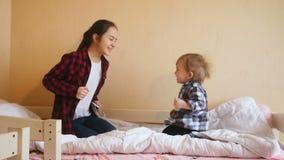 Adolescente allegro e felice che salta sul letto con il suo piccolo fratello del bambino archivi video