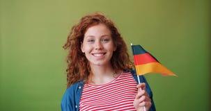 Adolescente allemande de charme tenant le drapeau national du sourire de l'Allemagne banque de vidéos