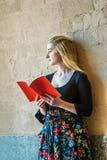 Adolescente americano que lee el libro rojo al aire libre en Nueva York Fotografía de archivo libre de regalías