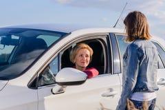 Adolescente amistoso que habla con un conductor femenino Imagen de archivo libre de regalías