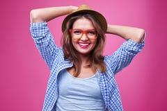 Adolescente ampliamente sonriente en los vidrios y el sombrero que detienen a Han Imagen de archivo
