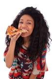 Adolescente américaine de jeune africain noir mangeant une tranche de pizz Photographie stock libre de droits