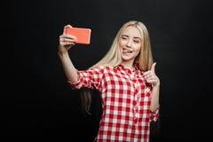 Adolescente animado que toma el selfie contra fondo negro Foto de archivo libre de regalías
