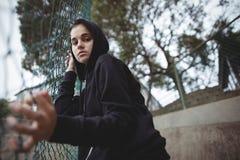 Adolescente ansioso che si appoggia il recinto della rete metallica alla città universitaria della scuola Fotografia Stock