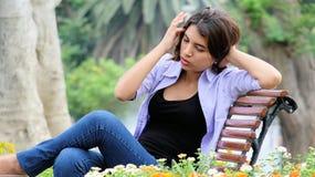 Adolescente ansioso de la muchacha que se sienta en banco Fotografía de archivo