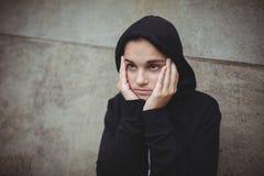Adolescente ansioso en la chaqueta con capucha negra que se coloca con la mano en cara Foto de archivo libre de regalías