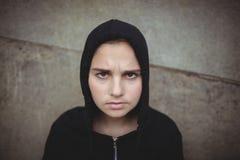 Adolescente ansioso en la chaqueta con capucha negra que se coloca en la escuela Fotos de archivo