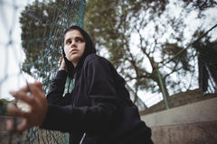 Adolescente ansioso que se inclina en la cerca de la malla de alambre Fotografía de archivo