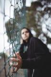 Adolescente ansioso que se inclina en la cerca de la malla de alambre Fotos de archivo libres de regalías