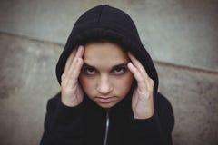 Adolescente ansioso in rivestimento incappucciato nero che esamina macchina fotografica Immagini Stock