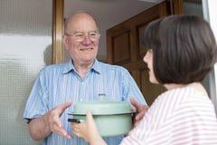 Adolescente apportant le repas pour le voisin masculin plus âgé images libres de droits