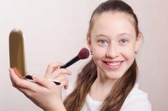 Adolescente aprende aplicar el polvo en su cara Fotos de archivo