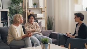 Adolescente arrabbiato che combatte con la madre nell'ufficio del terapista durante la consultazione stock footage