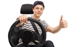 Adolescente asentado en el asiento de carro que da el pulgar para arriba Imágenes de archivo libres de regalías