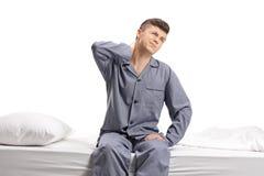 Adolescente asentado en una cama que experimenta dolor de cuello Imágenes de archivo libres de regalías