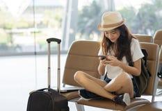Adolescente asiático da mulher que usa o smartphone no terminal de aeroporto que senta-se com mala de viagem e trouxa da bagagem  foto de stock