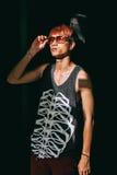 Adolescente asiático de la moda en gafas de sol del estilo con la caja de la guitarra Fotografía de archivo