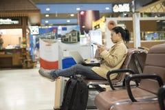 Adolescente asiático de la mujer que usa smartphone y el ordenador portátil en el término del aeropuerto foto de archivo