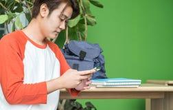 Adolescente asiático del hombre joven que usa el teléfono móvil que charla con el amigo Foto de archivo