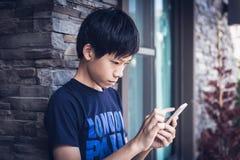 Adolescente asiático del muchacho que usa el smartphone, luz del día al aire libre Imagenes de archivo