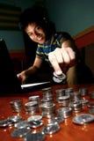 Adolescente asiático delante del ordenador portátil y de la viruta en una pila de monedas Foto de archivo