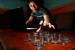 Adolescente asiático delante del ordenador portátil y el alcanzar para una pila de monedas Foto de archivo