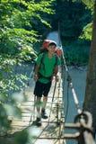 Adolescente asiático en puente colgante Fotografía de archivo