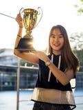 Adolescente asiático en ropa deportiva que soporta un trofeo al aire libre Imagen de archivo libre de regalías