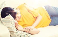 Adolescente asiático feliz que duerme en el sofá en casa Imagen de archivo