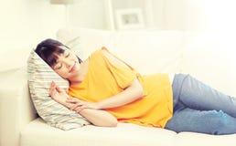 Adolescente asiático feliz que duerme en el sofá en casa Foto de archivo