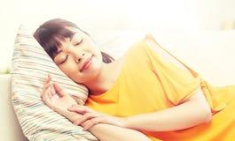 Adolescente asiático feliz que duerme en el sofá en casa Fotografía de archivo