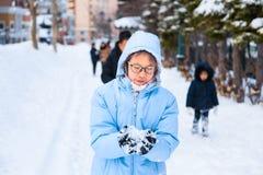Adolescente asiático feliz que se goza que juega nieve en un triunfo frío Foto de archivo libre de regalías