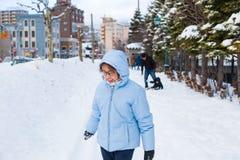 Adolescente asiático feliz que se goza que juega nieve en un triunfo frío Fotos de archivo