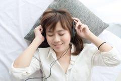 Adolescente asiático feliz que usa el auricular Imagen de archivo libre de regalías