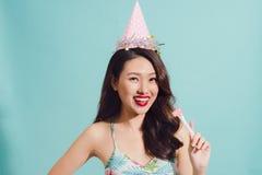Adolescente asiático femenino elegante que sostiene la piruleta sobre backgou azul Imagenes de archivo
