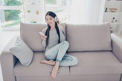 Adolescente asiático hermoso emocionado está escuchando la música en blanco grande Imagen de archivo