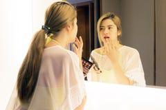 Adolescente asiático hermoso que aplica el lápiz labial su boca antes Fotografía de archivo