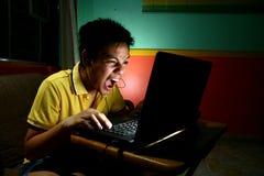 Adolescente asiático, intenso jugando o trabajando en un ordenador portátil Fotos de archivo libres de regalías